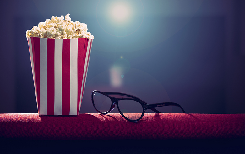 Popcorn and glasses on armchair at movies