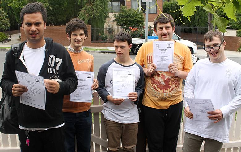 Five young men pose outside with certificates