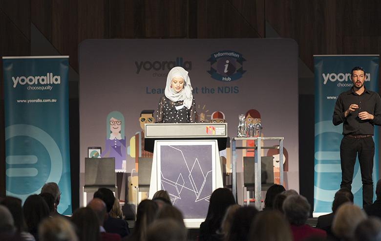 Susan Carland on stage addressing audience