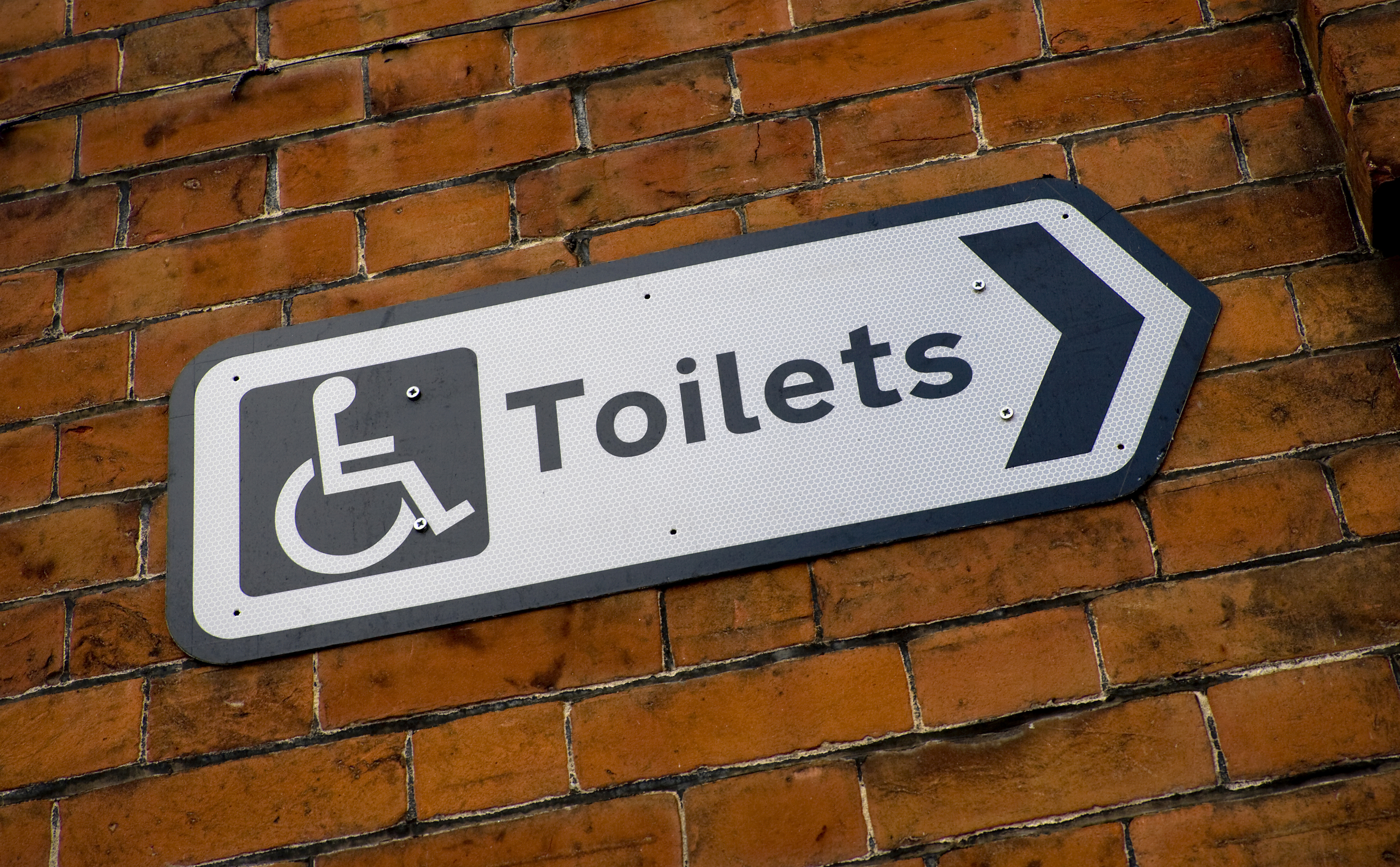 Sign pn brick wall pointing to accessible toilet
